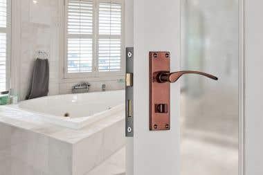 Sophia Lever on Backplate Bathroom Door Handle - Rose Gold/Copper On A White Wooden Glass Door